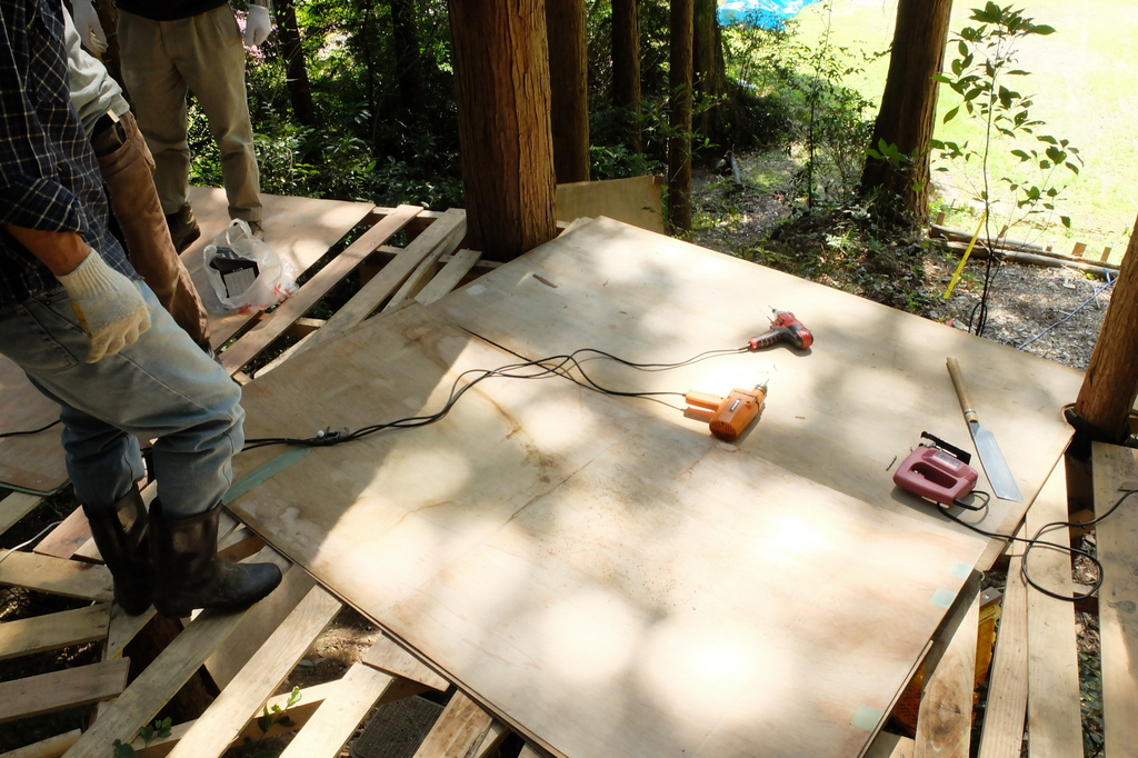 ツリーハウスステージの根太のうえにベニヤ板を敷いているところ。